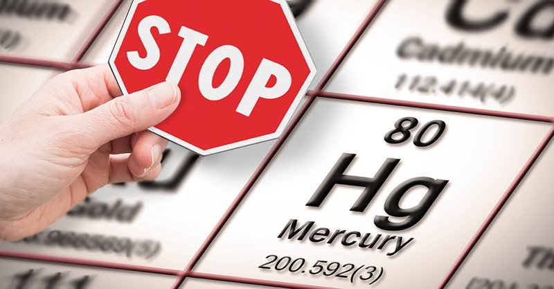 Hand holding stop sign sticker above Mercury on periodic table.