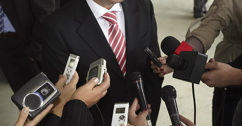 Microphones being held up to man in suit